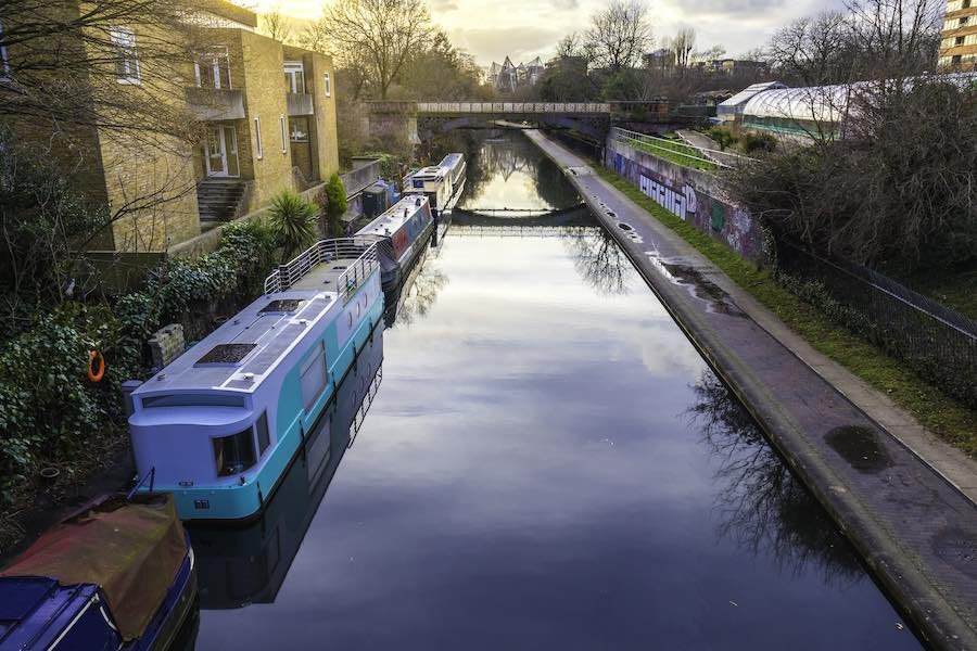 River canal with a bridge and house boats in the banks in West London